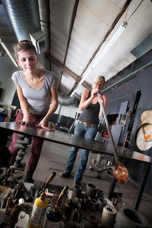 sculpting: Two glass artists working together on clear vase Stock Photo