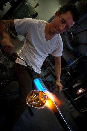Man working at a glass company with blowtorch photo