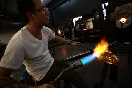 Glass art creation with blowtorch near blast furnace photo