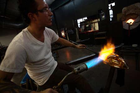 sculpting: Glass art creation with blowtorch near blast furnace Stock Photo