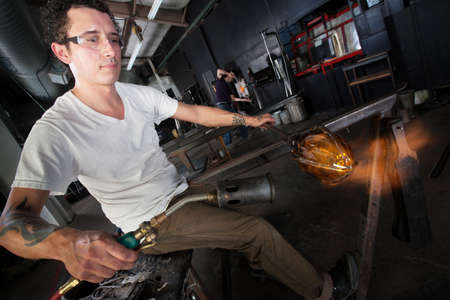 blowtorch: Art student holding glass piece blasted by blowtorch