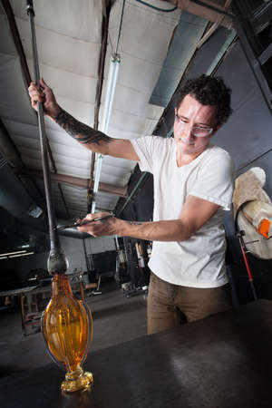 sculpting: Man with tattoo creating glass art object on workbench