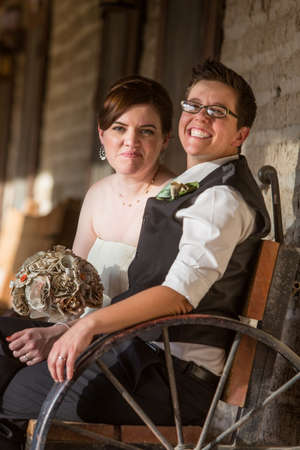lesbians: Smiling newlywed couple sitting on antique bench Stock Photo
