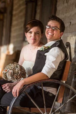 lesbianas: Sonriente pareja de recién casados ??se sientan en banco de antigüedades