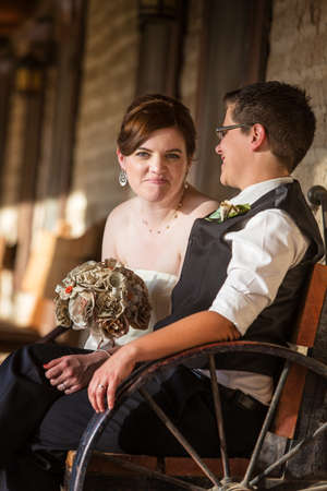 Happy bride with partner on antique bench photo