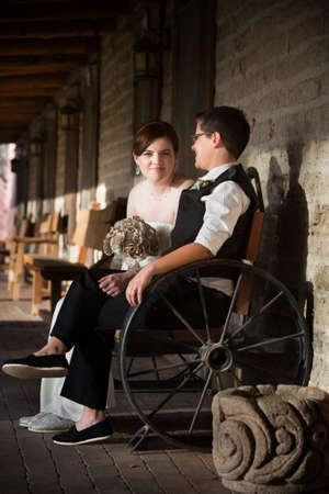 butch: Lesbian newlyweds sitting together in rustic setting Stock Photo