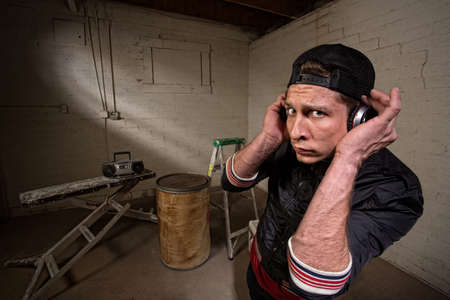 European hip hop guy with backwards cap and earphones Stock Photo - 19144244