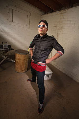 Posing Caucasian rapper in basement with hands on hips photo