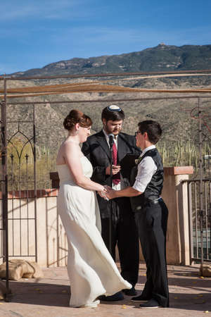 Rabbi reading sacrament for happy lesbian couple marring outdoors Stock Photo - 19248356