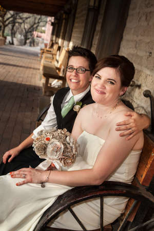Caucasian lesbian newlyweds sitting on rustic bench Stock Photo - 19248355