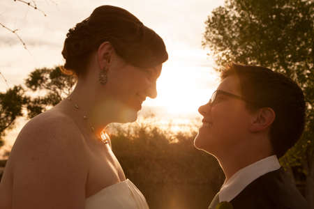 Same sex female bride and groom outdoors by sunset Stock Photo - 19242542