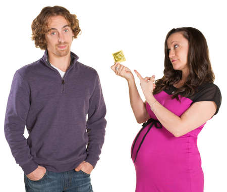 Frustrated man and pregnant woman pointing at condom photo