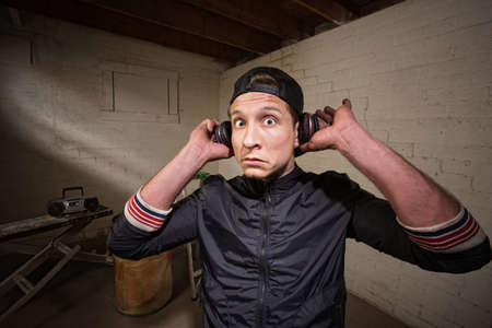 Surprised young man holding earphones over ears photo