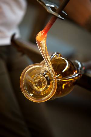 Close up of red hot molten glass with pliers