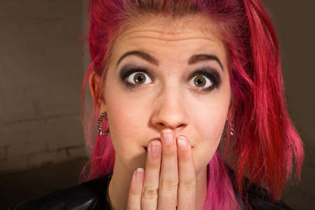 suspense: Young punk rocker in pink hair with hand on mouth