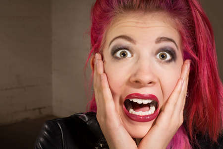 horrified: Horrified young punk rocker female in pink hair Stock Photo