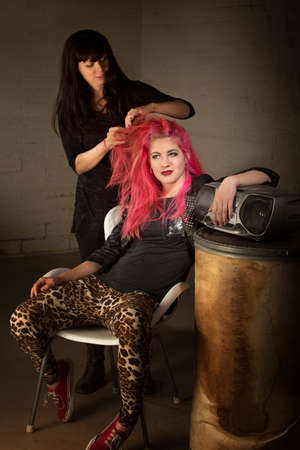 fashion shoot: Young punk rocker leaning back with hair stylist working
