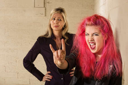 disapproving: Teenager in pink hair with disapproving mother in background Stock Photo