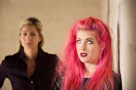 Annoyed girl in pink hair with upset parent