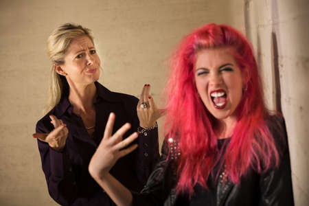 disapproving: Loud teenage girl in pink hair with disapproving mother Stock Photo