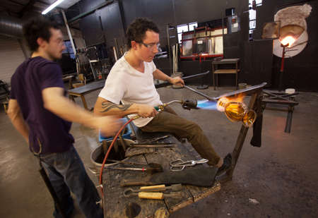 blowtorch: Two glass artists working together with blowtorch Stock Photo