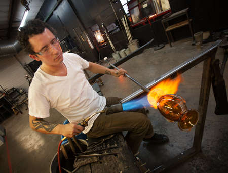 sculpting: Adult male working in glass artist studio with blowtorch