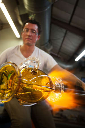 shaping: Latino glass artist sculpting glass vase with blowtorch Stock Photo