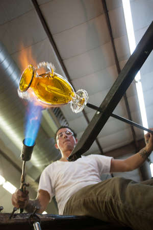 sculpting: Industrial artist creating a yellow glass vase