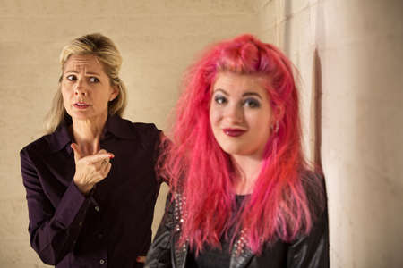 embarrassed: Concerned mother pointing at grinning daughter in pink hair Stock Photo