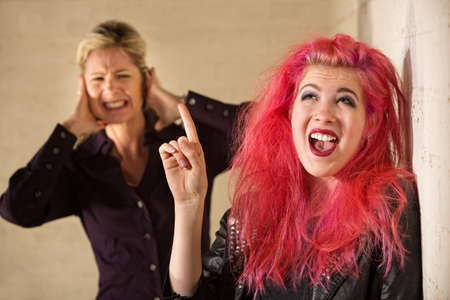 Woman covering ears while woman in pink hair sings photo