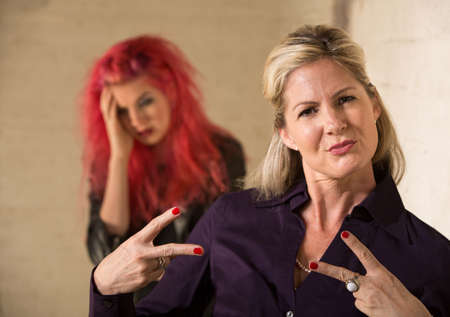 Cool mother making hand gesture with embarrassed teenager photo