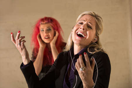 embarrassed: Happy woman singing loudly with annoyed teenager nearby Stock Photo