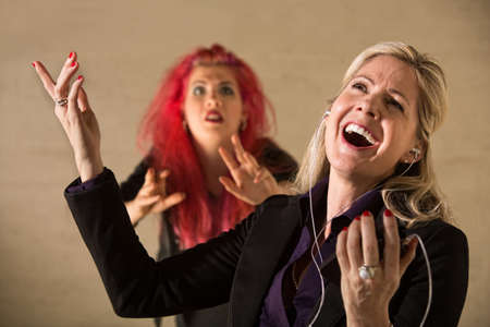 gullible: Embarrassed teen in pink hair with singing parent holding mp3 device