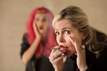 embarrassed: Surprised teen behind mature woman smoking a cigarette Stock Photo