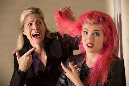 Shocked blond woman holding pink hairdo of teenager