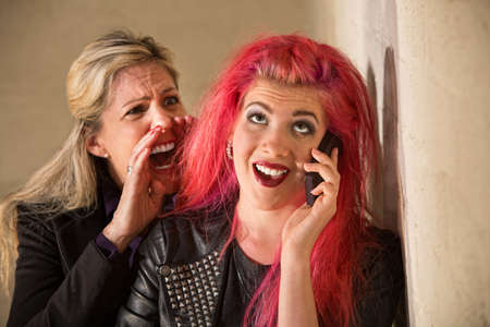 Mature woman yelling to ear of teenager on phone photo