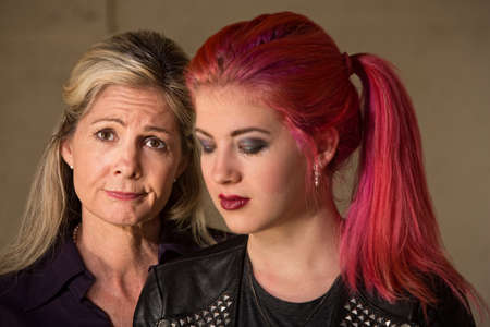 Mature woman with teenage girl in pink hair looking down photo