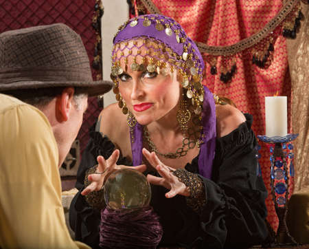 fortune teller: Sexy fortune teller waving hands over crystal ball Stock Photo