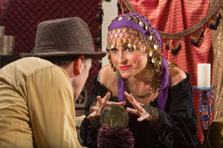 Grinning European fortune teller with hands over crystal ball photo