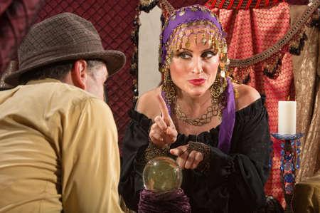 Pretty zigeuner dame wijst met een vinger over kristallen bol