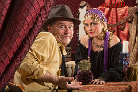 gullible: Fortune teller in head scarf with skeptical customer and crystal ball Stock Photo