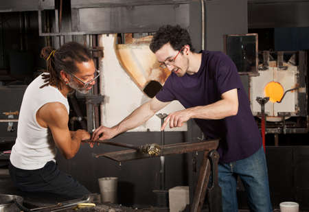 Two glass artisans working together on small vase photo