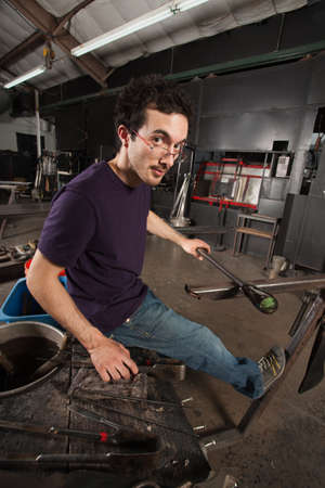 Serious young adult with tools and workbench in glass factory photo