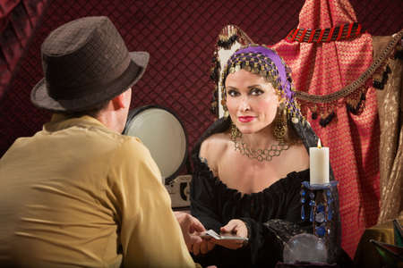 gypsy woman: Sexy fortune teller with businessman and candle