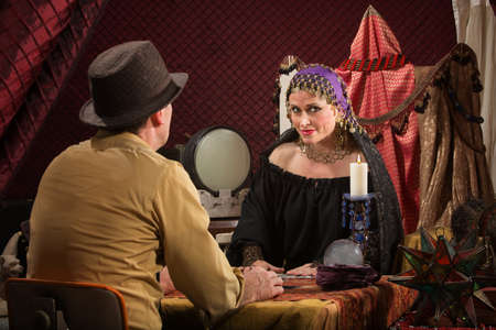 soothsayer: Smiling beautiful fortune teller with crystal ball and customer Stock Photo