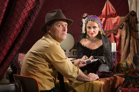 bad fortune: Man with fortune teller worried about bad luck
