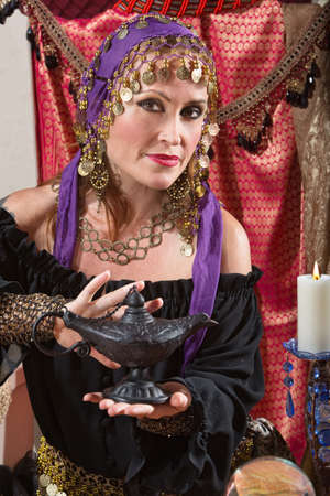 Pretty female gypsy fortune teller rubs a magic lamp photo