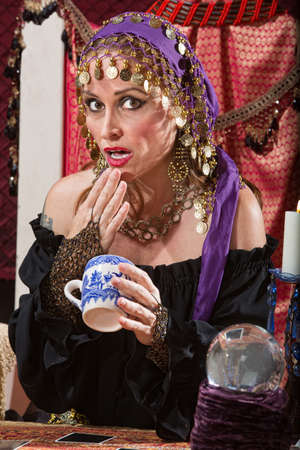 gypsy woman: Surprised fortune teller reading tea leaves cup