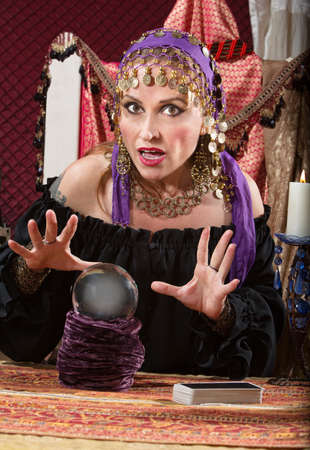 Charming Caucasian woman in headscarf waving hands over crystal ball photo