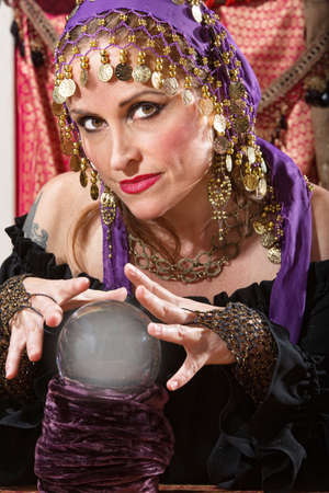 Pretty lady waving hands over crystal ball photo